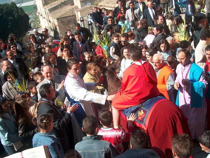 foto dei fedeli che portano le palme accanto all'asinello e Gesu'
