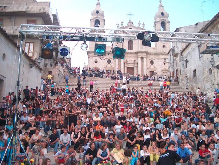 foto di gente seduta sugli scalini della chiesa madre in attesa dello spettacolo alle ore 19 circa
