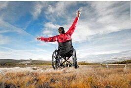 Disabile in carrozzina che tocca il cielo con le mani
